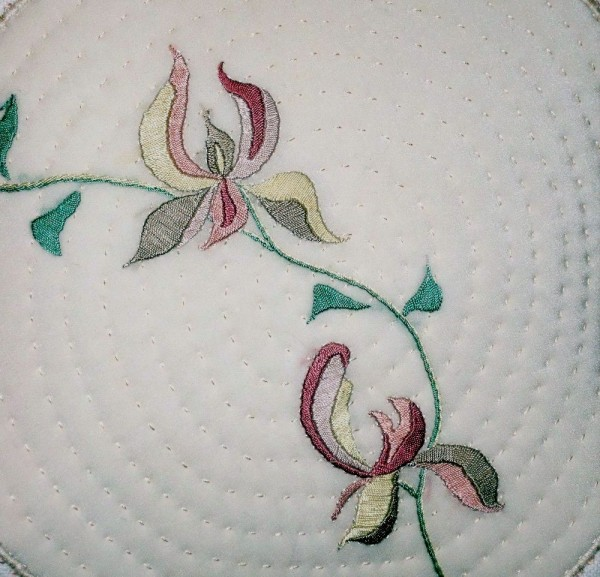 Cushion showing detail of stylised magnolia (hand embroidered)