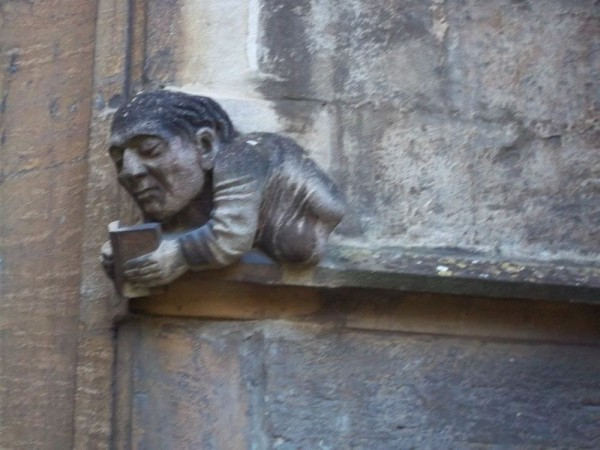 Grotesque on the outside of Balliol College Library showing the self absorption of reading