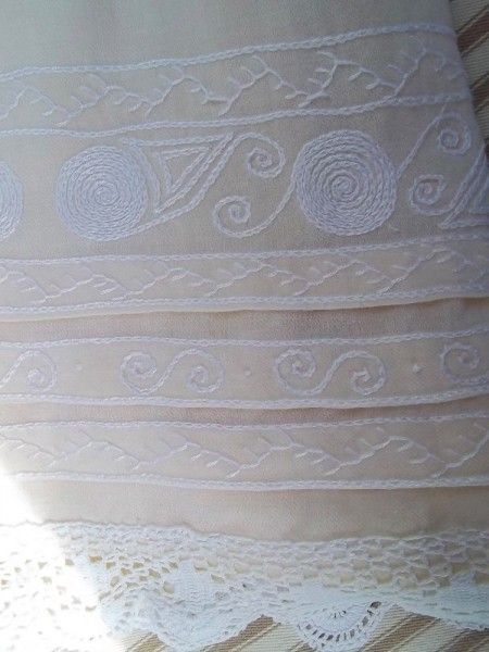Christening dress in English Smock Embroidery: detail of concentric circles (wheel shapes suggest the trades of carter or wagoner.)