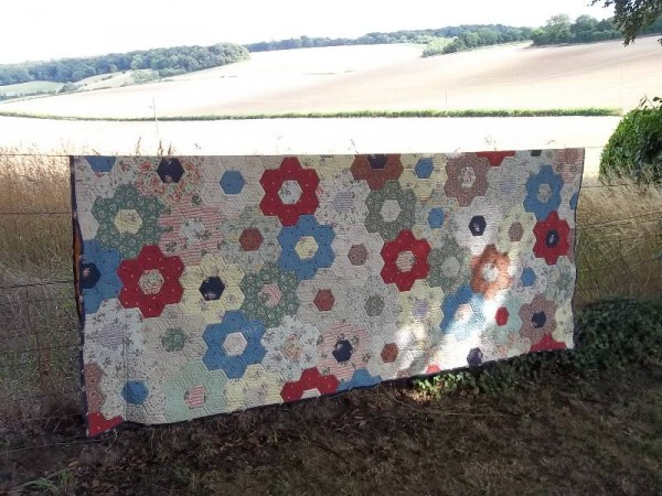 Grandmother's flower garden quilt - used as a curtain but having a brief airing in the garden