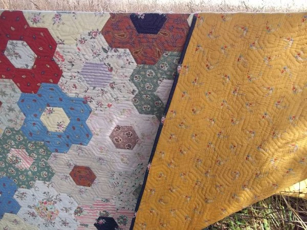 Grandmother's garden quilt showing golden Liberty lawn backing fabric