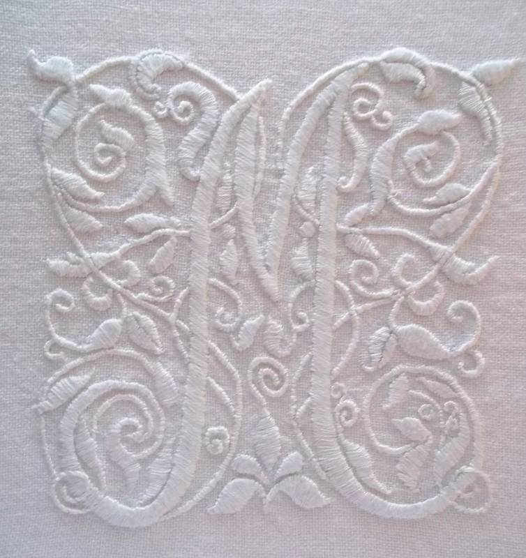 The fanciful letter: M. Hand embroidery in white embroidery thread on white linen by Mary Addison