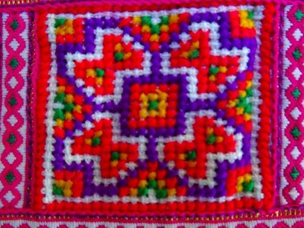 Detail of modern Vietnamese purse showing cross stitch panel.  Though the dyes look to be synthetic rather than natural,, the workmanship is still excellent.