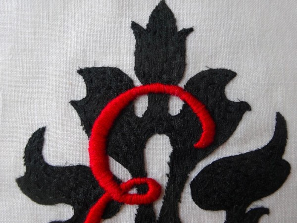 Scarlet and black monogrammed E: close up of detail