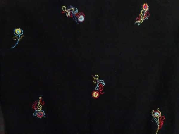 Brightly embroidered feathers on black cashmere (hand embroidered by Mary Addison)