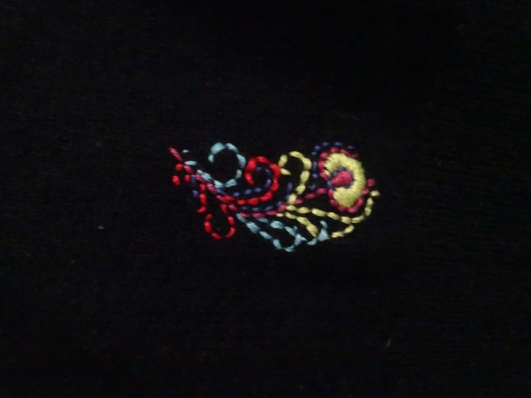 Brightly embroidered feather on black cashmere (hand embroidered by Mary Addison)