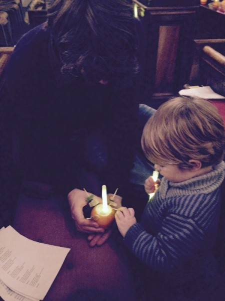 Grandson and son-in-law assembling a Christingle