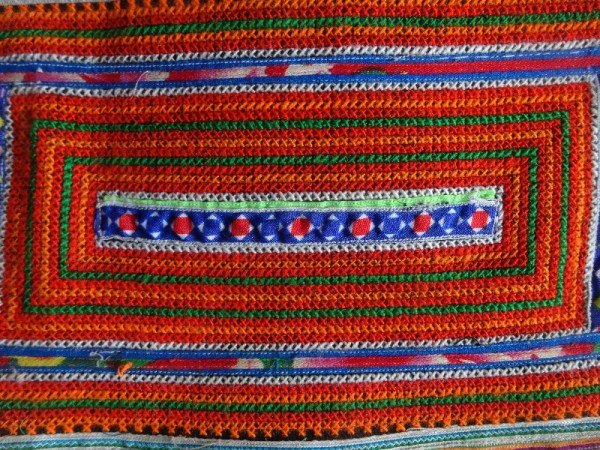 Red Mong skirt : detail of cross stitch and appliquéd ribbon border